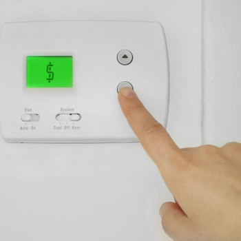 34329957 - person adjusting a wall thermostat with dollar sign symbol on the display